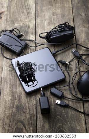 Battery charger and wires tech mess on table - stock photo