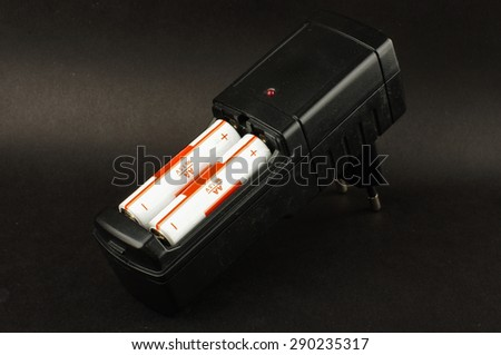 Battery charger with loaded batteries isolated on the black background - stock photo
