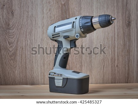 Battery screwdriver or drill, on wooden background, close up. - stock photo