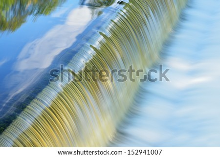 Battle Creek River cascade captured with motion blur and with reflections of trees and sky in calm water, Michigan, USA  - stock photo