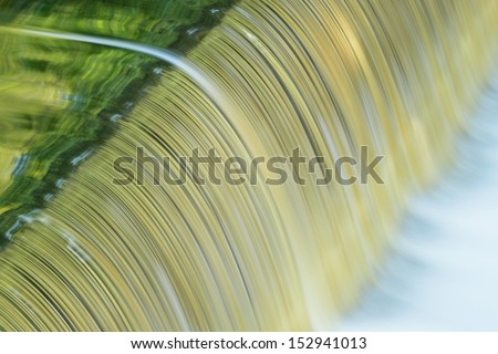 Battle Creek River cascade captured with motion blur and with reflections of trees in calm water, Michigan, USA  - stock photo
