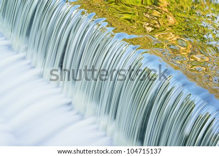 Battle Creek River cascade with abstract reflections of trees in calm water, Michigan, USA - stock photo