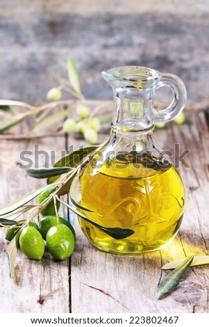 Battle of olive oil with olive branch over wooden table. - stock photo