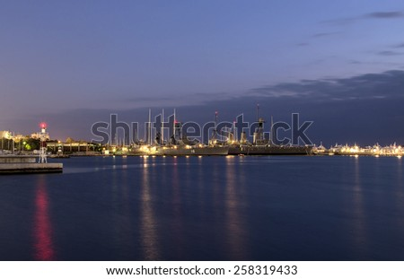 Battleship in harbor at night - stock photo