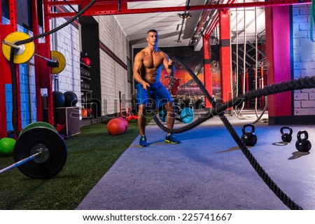 battling ropes man at gym workout exercise fitted body - stock photo