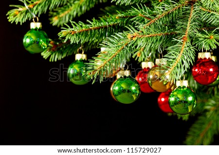 Baubles on Christmas tree isolated on black - stock photo