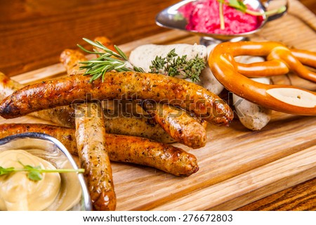 Bavarian fried sausages and pretzel - stock photo