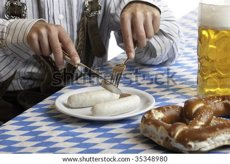 Bavarian man dressed in traditional leather trousers (lederhosen) is eating a veil sausage (Weisswurst) and beside him is a full beer stein (Mass) and pretzel. - stock photo