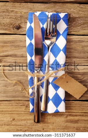 Bavarian table setting in a tavern or restaurant with a knife and fork tied with raffia and a tag on a blue and white napkin in the Bavarian colors ready for Oktoberfest - stock photo