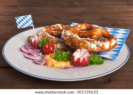 Bavarian vegetarian breakfast with two soft pretzels and cheese delicacy with plate on wooden board from Germany - stock photo