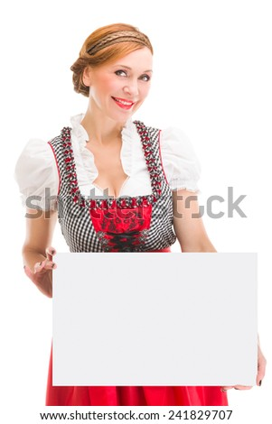 Bavarian woman in dirndl, holding blank signboard. - stock photo