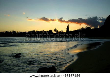 Bay brightens with sun's rising.  Tinted waters reflect the golden, orange and pink morning sky.  Kauai, Hawaii. - stock photo