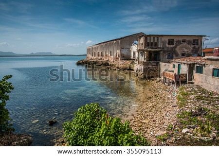 Bay in old colonial cuban city of Gibara, with old port building - stock photo