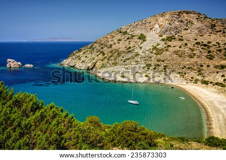 Bay in Syros island, Cyclades, Greece, with clear transparent waters and an anchored sailing boat.  - stock photo