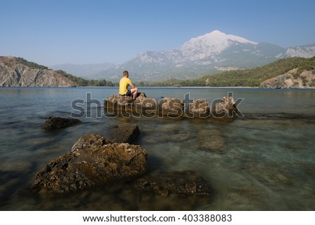 Bay to sea shore. Summer landscape. Tourist sits on a rock and looking at the mountains. Turkey Phaselis Bay, Mount Tahtali - stock photo