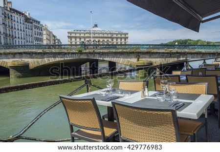 Bayonne, France - May 21, 2016: Bistro terrace next to Pont Mayou, bridge over Le Nive river with Hotel de ville (City Hall) of Bayonne, called Mairie de Bayonne, in background. Aquitaine, France - stock photo