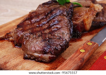 bbq beef meat fillet on wooden plate with cutlery - stock photo