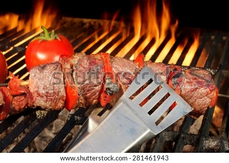 BBQ Beef Shish Kebabs Close-up On The Hot Charcoal Grill With Bright Flames Of Fire On The Isolated Black Background - stock photo