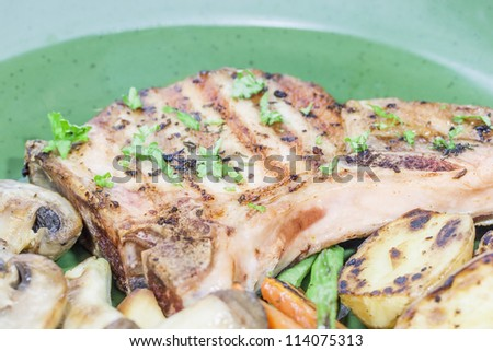 Bbq bone in pork chop and bbq button mushroom, baby potato, baby carrot and green pea. - stock photo