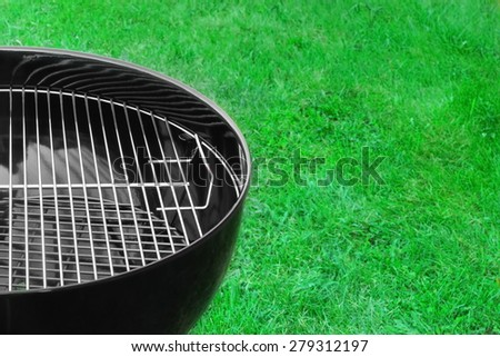 BBQ Charcoal Kettle Grill Close-up On The Spring Grass Background - stock photo