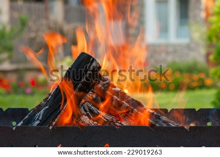 BBQ. Firewood and fire in brazier. - stock photo