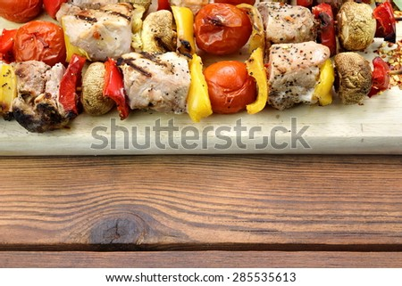 BBQ Grilled Mixed With Vegetables Pork Kebabs On The Wooden Cutting Board - stock photo