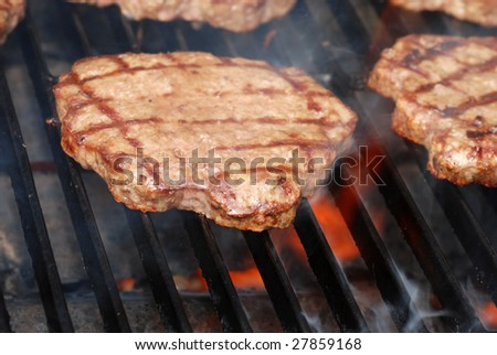 BBQ hamburger on the grill with flames - stock photo