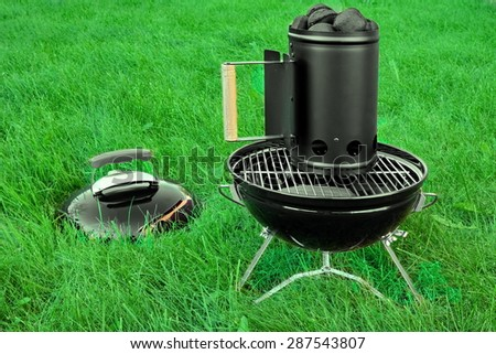 BBQ Kettle Portable Grill Appliance With Charcoal Briquettes Starter On The Summer Lawn, Picnic Or Cookout Concept - stock photo