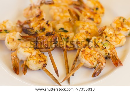BBQ Prawns - Grilled prawn skewers on a white plate /  background. Selective focus and shallow DOF. - stock photo