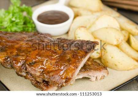 BBQ Ribs - Marinated pork ribs with potato wedges and barbeque sauce. - stock photo