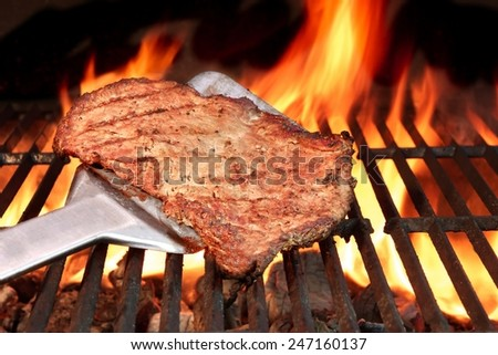 BBQ Roasted Beef Steak on the Turner and Flaming Charcoal Grill - stock photo