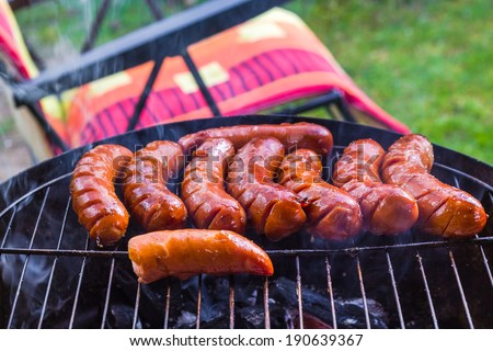 BBQ with fried sausages on the grill - stock photo