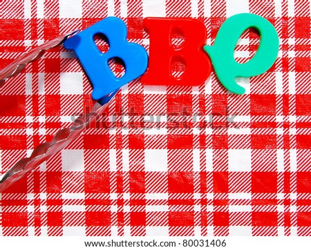BBQ written in colorful plastic letters, held by tongs on a background of a picnic tablecloth - stock photo