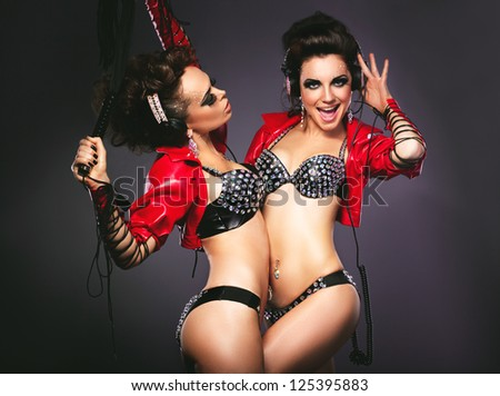 Bdsm. Playful Women in Sexy Costumes with Lash - stock photo