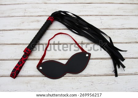 BDSM Toy, A black and red BDSM toy, a whip and mask over a distressed wood background - stock photo