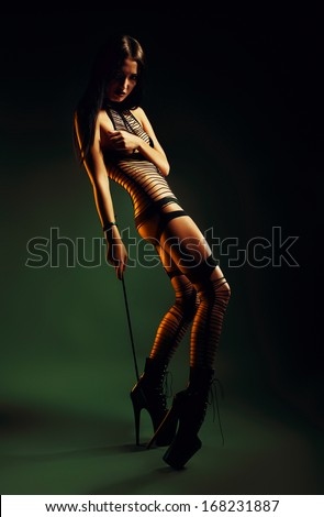 bdsm woman with whip in yellow light - stock photo
