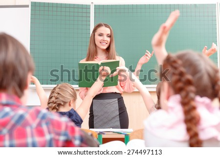 Be first. Little pupils raising their hands during classes and teacher explaining new material. - stock photo