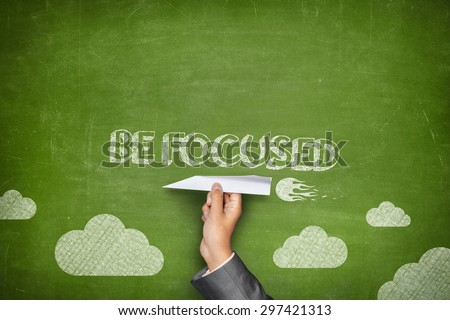 Be focused concept on green blackboard with businessman hand holding paper plane - stock photo