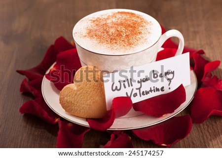 Be my Valentine. Closeup image of lovely heart shape cookie with Valentine day message and cup of coffee arranged with copy space on wooden table and decorated with rose petals - stock photo