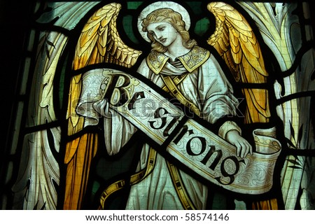 Be Strong, horizontal An angel holding the banner reading Be Strong. Fragment of a memorial stained glass window created in 1911 to commemorate a soldier killed during World War One. - stock photo