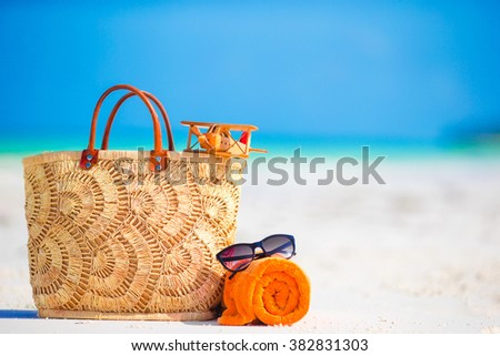 Beach accessories - toy plane, straw bag, orange towel and unglasses on the beach - stock photo