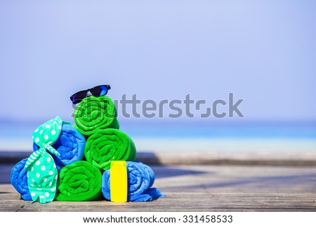 Beach and summer vacation accessories concept - closeup towels, sunglasses and sunblock - stock photo