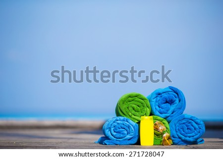 Beach and summer vacation accessories concept - colorful towels, sunglasses and sunscreen  - stock photo