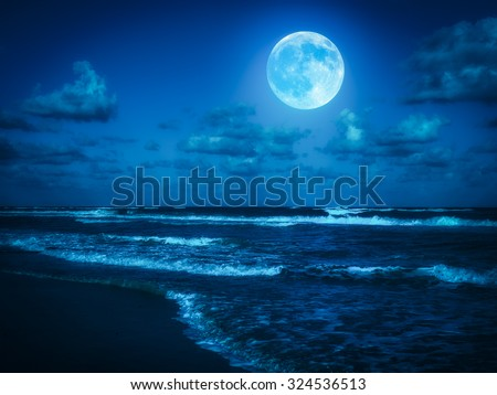 Beach at midnight with a full moon shining on the sky - stock photo