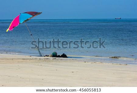 Beach background with blue sea, stripped beach umbrellas. - stock photo