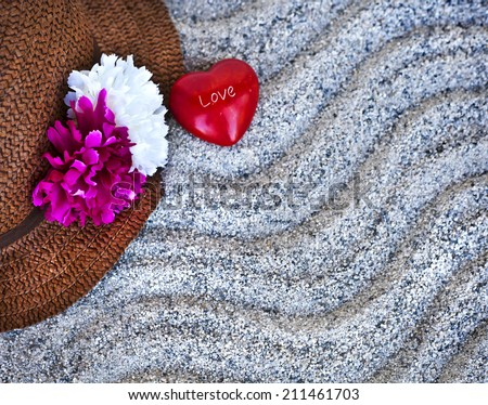 Beach background with copyspace, beach sand summer theme, straw hat and little red heart with letters LOVE over sand texture - stock photo