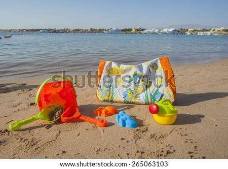 Beach bag and childrens toys on a tropical beach by the sea - stock photo