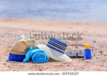 Beach Bag and Supplies for Day at the Beach on Sandy Shore - Sun Hat, Flip Flops, Towel, Sunscreen Lotion, and Beach Bag on Sunny Beach - stock photo