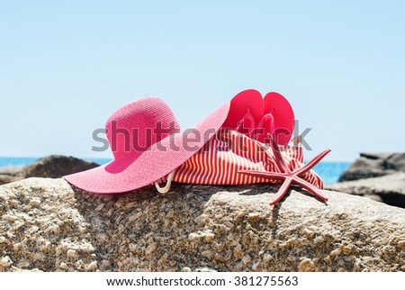 Beach Bag Flip Flops Sea Star Hat Stones Overlooking Ocean Summer Holiday Concept  - stock photo