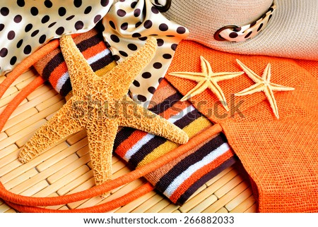 Beach bag, starfish, beach hat, towel on a wooden background - stock photo